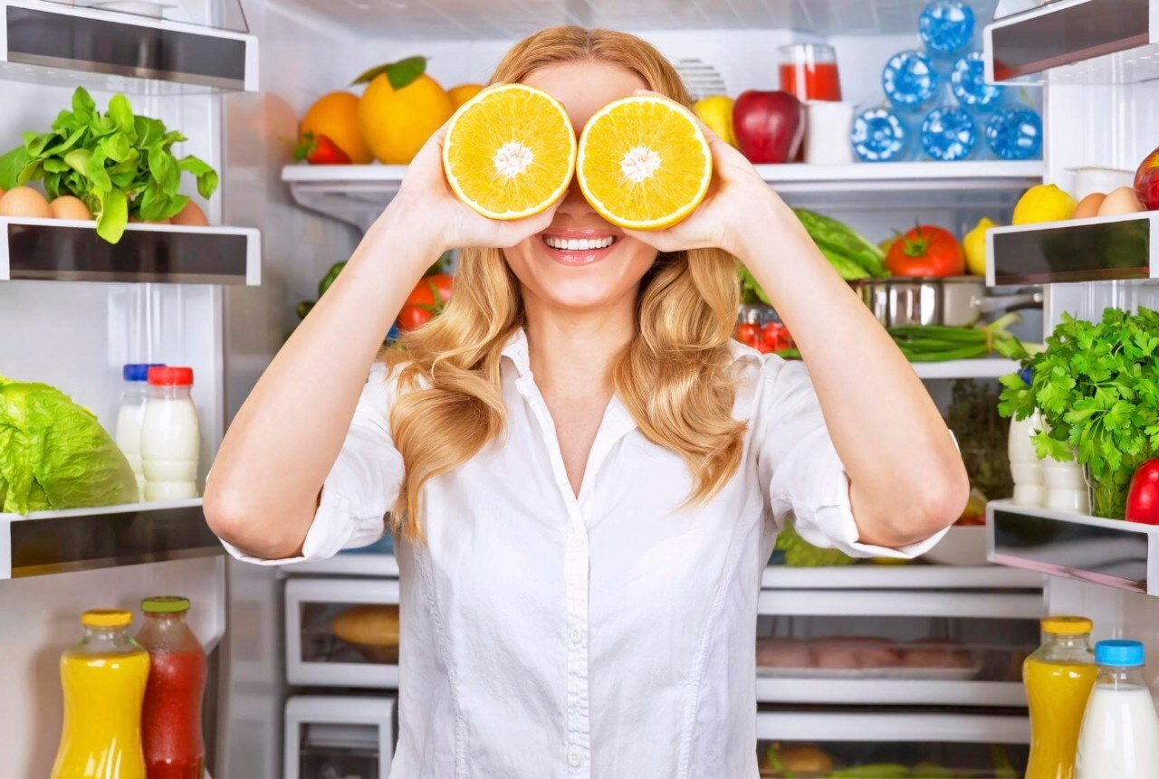 Joyful female on the kitchen playing with two half of orange, tasty juicy fruit instead eyes, healthy nutrition, fun and joy concept
