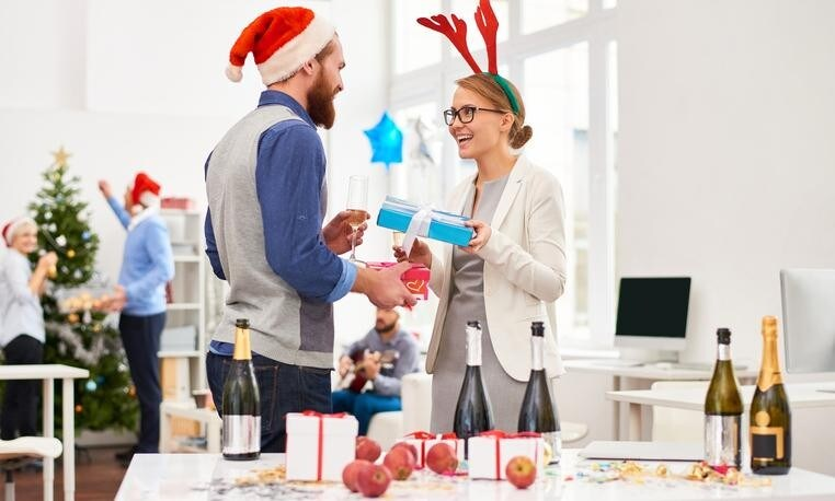 Friendly office workers giving presents to each other at office party