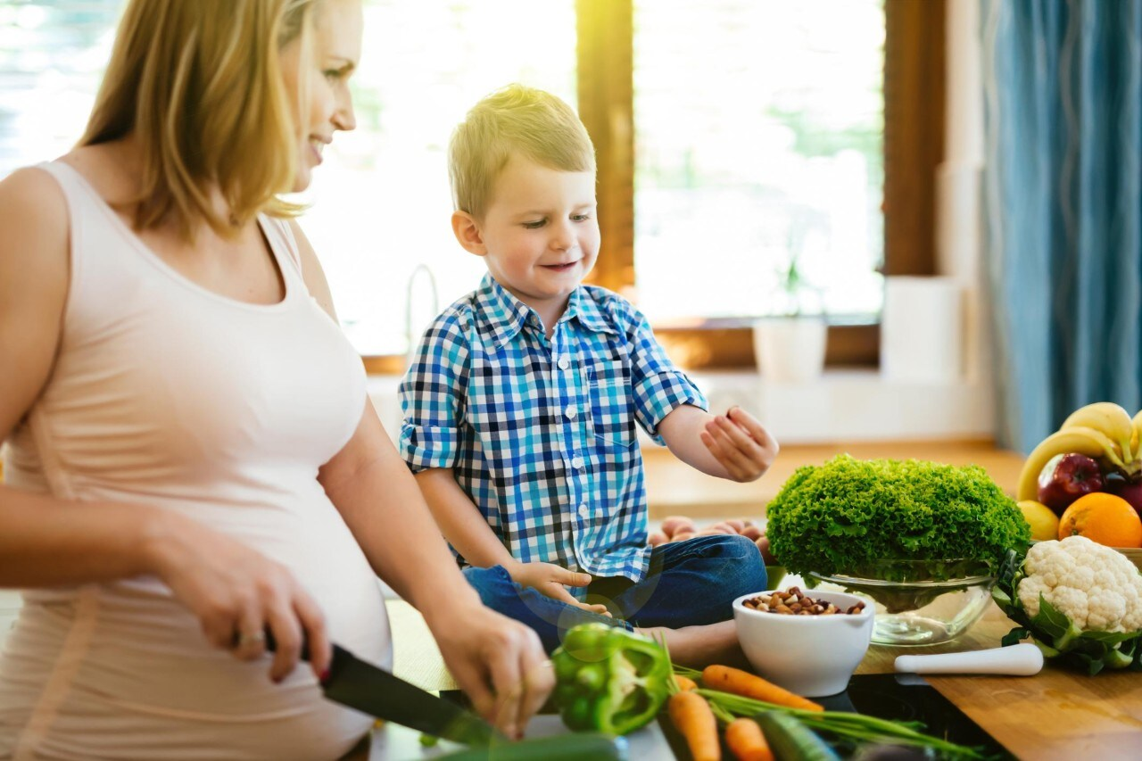 Pregnant woman preparing meal with son from fresh vegetables