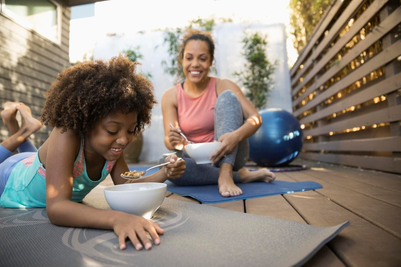 African American mother and daughter eating cereal on yoga mats on deck
