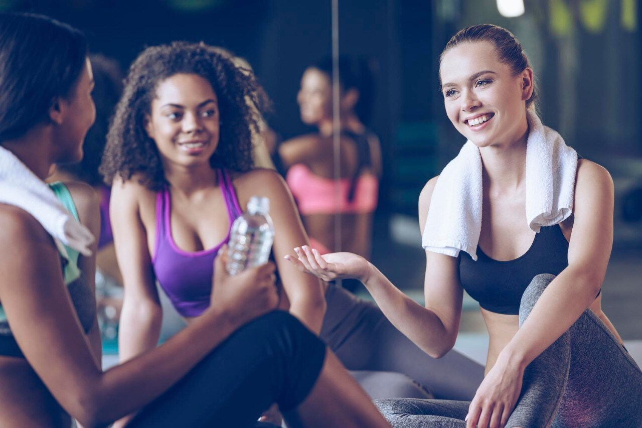 Beautiful young women in sportswear discussing something with smile while sitting on exercise mat at gym