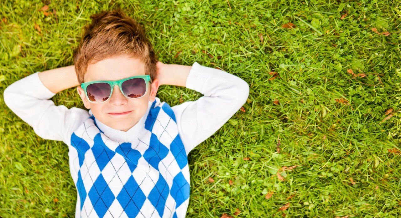 Portrait Of A Boy Wearing Sunglasses Relaxing On Green Grass